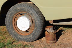 Rusted old milk can. A rusted old milk can next to the wheel of an old and abandoned vehicle Stock Photo