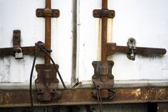 The rusted old trailer is closed to padlocks and tied with a rub. Old rusted semi trailer door closing mechanism fulfilled its technical resource and became Stock Images