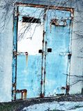 Rusted Blue Painted Doors. Rusted old twin  exterior metal doors, with faded blue paint, on a disused concrete  bunker Royalty Free Stock Photography
