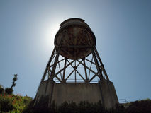 Rusted out Water Tower with sun directly behind it royalty free stock photos