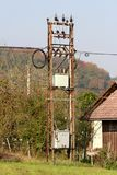 Rusted outdoor grey metal electrical high voltage box with ceramic insulators connected with electrical wires surrounded with. Dense trees on clear blue sky stock photo