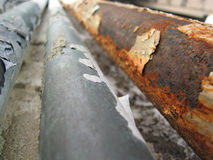 Rusted Pipes. Rusted metal plumbing attached to wall running away from the viewer towards the horizon royalty free stock photography