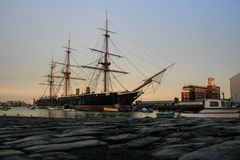 Rusted Railing in Southsea, Portsmouth. HMS Warrior during a peaceful sunrise in Portsmouth historic dockyard. The ship was built and used by the Royal Navy in Royalty Free Stock Photos