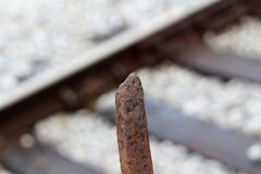 Rusted railroad spike. S with railroad as blurred background in Columbus, Mississippi royalty free stock photos