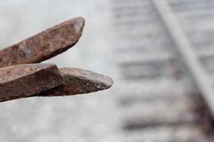 Rusted railroad spike. S with railroad as blurred background in Columbus, Mississippi royalty free stock image