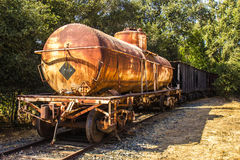 Rusted Railroad Tanker Car with Storage Cars Attached Royalty Free Stock Image