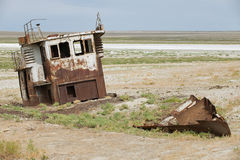 Rusted remains of fishing boat at the sea bed of the Aral sea, Aralsk, Kazakhstan. Evaporation of formerly one of four largest lakes in the world is considered Stock Photography