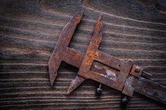Rusted Retro--redete Tasterzirkel auf dunklem constru hölzernes Brett der Weinlese an Lizenzfreie Stockfotos