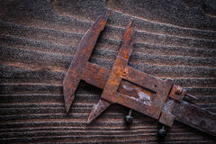Rusted retro-styled caliper on vintage dark wooden board constru Royalty Free Stock Photos