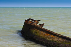 Rusted ship wreck in sea. Rusted wreck of ship or boat lying on side in sea Stock Images