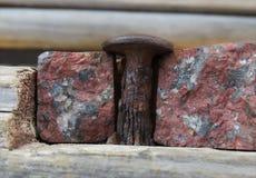 Rusted spikar i bruten granit Arkivfoto