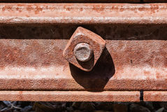 Rusted square bolt in metal rail. Stock Photo