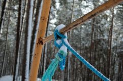 Rusted swing set metal with blue rope tied around metal structure Royalty Free Stock Images