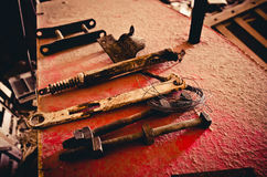Rusted tools lined up on a weathered red piece of metal. Various farm tools laying inside a barn Stock Images