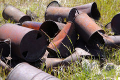 Rusted Trash Cans. Pile of old rusted tin cans as trashed dumped out in grass Stock Photo