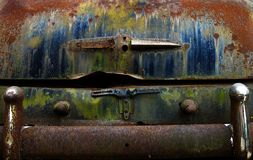 Rusted trunk with colorful peeling paint and chrome bumper old junk car on Route 66 stock image