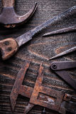 Rusted vintage measuring calipers hand saw and claw hammer on vi Stock Photo