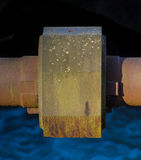 Rusted water pipe over water stream Royalty Free Stock Photography