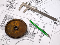 Engineering background. Rusted wheel, caliper and pencil on engineering drawings background Royalty Free Stock Photography