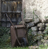 Rusted wheelbarrow. And old stone wall Stock Images