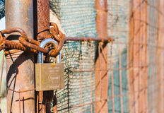 Rusted wire netting. In industrial place. Particular of a padlock Stock Images
