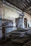 Rusted Worn Interior of Old Industrial Building with Machines and Stack of Tin royalty free stock photos