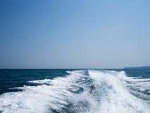 Rusteloos schuimend blauw overzees kielzogwater op de zeewateroppervlakte met duidelijke blauwe hemel terwijl reis door snelheids stock afbeeldingen