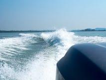 Rusteloos schuimend blauw overzees kielzogwater op de zeewateroppervlakte met duidelijke blauwe hemel terwijl reis door snelheids stock foto's