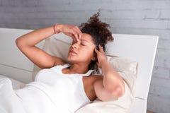 Rusteloos zwarte die aan slaap in bed proberen royalty-vrije stock afbeeldingen