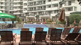 Rustend door de pool in de woon complexe Smaragd in Ravda, Bulgarije stock videobeelden