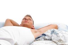 Rustende jonge mens die bovenkant in bed kijkt Royalty-vrije Stock Foto's