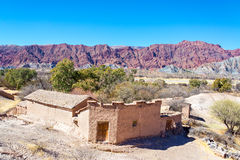 Rustic Adobe Building and Red Hills Stock Photography