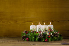Rustic  advent wreath or crown with four burning white candles. Royalty Free Stock Images