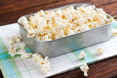 Rustic aluminum pan with popcorn. Horizontal photo of old aluminum pan which is placed on white green towel. All is on old dark wooden board. Pan is full of royalty free stock photos