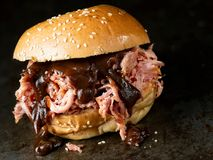 Rustic american barbecued pulled pork sandwich. Close up of rustic american barbecued pulled pork sandwich stock photo