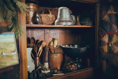 Rustic Antique Kitchen Cabinet With Kitchen Utensils. A rustic antique cabinet full of antique kitchen utensils. A vintage quilt and painting are draped over the Stock Image