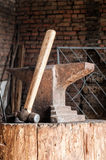 Rustic anvil and hammer on wooden stump. Royalty Free Stock Image