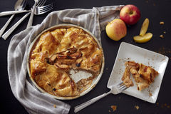 Rustic Apple Pie. An apple pie with a slice removed and ready to be served. Some silverware and apples are on the table in preparation stock images