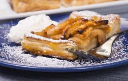 Rustic apple tart with an apricot glaze and powdered sugar. Piece of an apple tart baked in puff pastry with an apricot glaze dusted in powdered sugar and served Stock Images