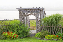 Rustic Arbour. Dense fog rolls in on a seaside garden with a very rustic arbor that was left to go natural with the elements Royalty Free Stock Photo