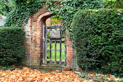 Rustic Arched Gateway. Rustic red brick Arched Gateway with fallen Autumn leaves on the ground Royalty Free Stock Image