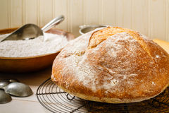 Rustic Artisan Bread. Round rustic artisan bread rests on a vintage wire cooling rack surrounded by a baking utensils and an old wood bowl full of flour Royalty Free Stock Photography