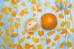 Rustic background. Exotic fruits. An overhead photo of tangerine without peel. Peeled juicy tangerine on the wooden blue table and. A lot of pieces of orange Royalty Free Stock Photos
