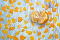 Rustic background. Exotic fruits. An overhead photo of tangerine without peel. Peeled juicy tangerine on the wooden blue table and. A lot of pieces of orange Royalty Free Stock Photography
