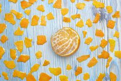 Rustic background. Exotic fruits. An overhead photo of tangerine without peel. Peeled juicy tangerine on the wooden blue table and. A lot of pieces of orange Stock Photos