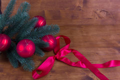 Rustic background with fir branch red Christmas balls and ribbons Royalty Free Stock Images