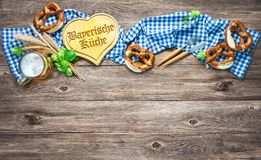 Rustic background for Oktoberfest or Bavarian specialties. With white and blue fabric, hop, silverware, beer glass and pretzels on wooden table. Menu card for royalty free stock photography