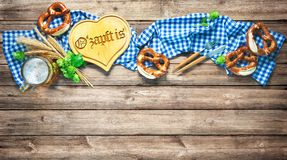 Rustic background for Oktoberfest or Bavarian specialties. With white and blue fabric, hop, silverware, beer glass and pretzels on wooden table. Menu card for royalty free stock image