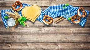 Rustic background for Oktoberfest or Bavarian specialties. With white and blue fabric, hop, silverware, beer glass and pretzels on wooden table. Menu card for stock photo