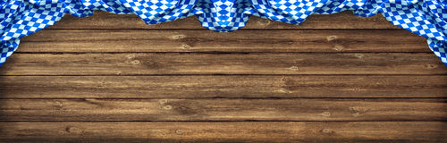 Rustic background for Oktoberfest. With Bavarian white and blue fabric on old wooden board royalty free stock image